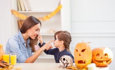 Cheerful young mother and girl are celebrating Halloween. They are sitting at the table and smiling. They are touching each other noses with joy. There are food and pumpkins on the table