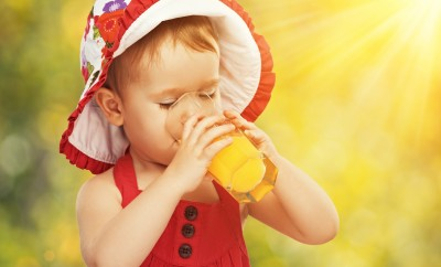 baby girl drinking orange juice in the summer outdoors